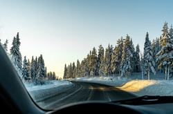 Driving along a slippery icy highway in a winter woodland. Drivers perspective, blurred foreground.