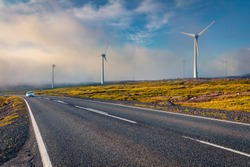 Driving among the field of wind turbines. Foggy summer scene of Faroe Islands, Denmark, Europe. Ecology concept background.