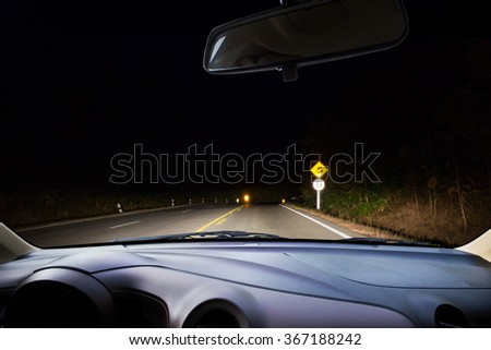 Driving at night in the woods .
