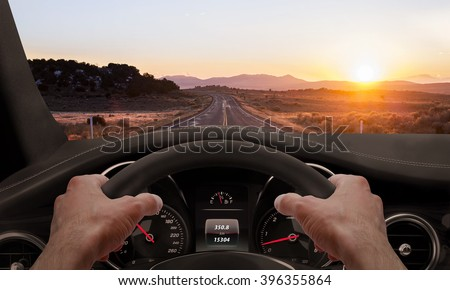 Driving at sunset. View from the driver angle while hands on the wheel.