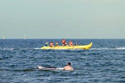 driving banana boat with seven adults and children racing on the water and through the waves at the Ostssee with a capsized surfer in the foreground and sailors in the background.