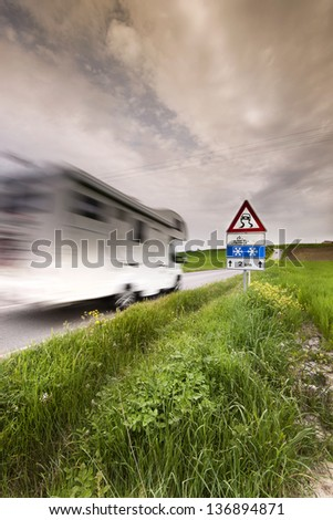driving camper on a country road skid sign