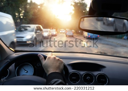 Driving car around town in sunny end of a day