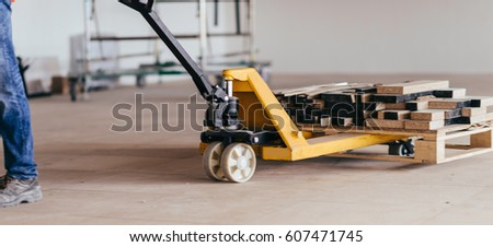Driving construction material with hand pallet truck