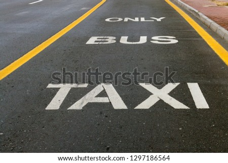 Driving directions Bus and Taxi lane sign painted on street #1297186564