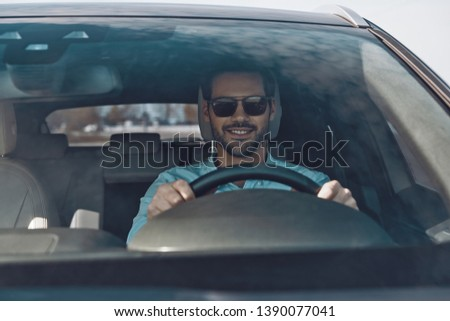 Driving his brand new car. Handsome young man smiling while driving a status car