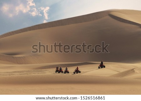 Driving off-road with quad bike or ATV vehicles. Namib sand desert on the background Stock photo ©