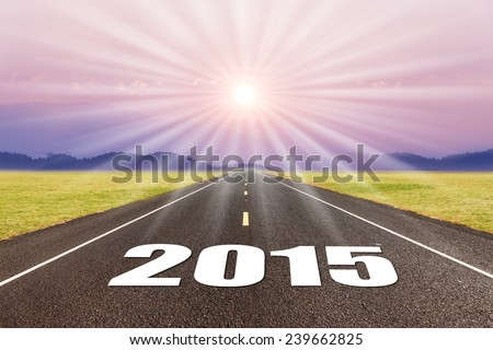 Driving on an empty road at sunset to upcoming 2015