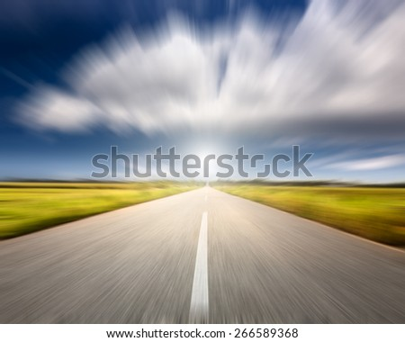 Driving on an empty road towards the big cloud at beautiful sunny day in motion blur