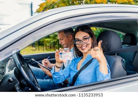 Driving school. Beautiful young woman successfully passed driving school test. She looking sitting in car, looking at camera and holding driving license in hand. Girl with driving license  #1135233953