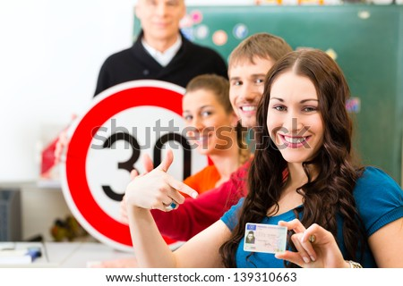 Driving school - driving instructor in his class and a female student driver looking in the Camera, in the background are traffic signs