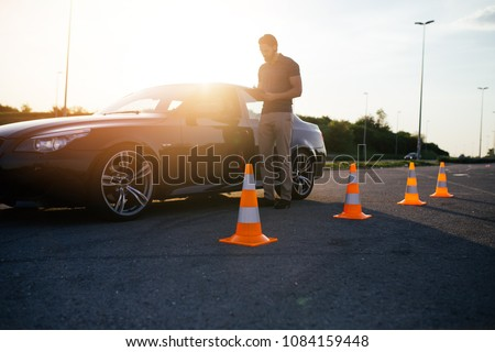 Driving school or test. Beautiful young woman with instructor learning how to drive and park car between cones. #1084159448