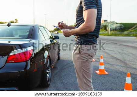 Driving school or test. Driving instructor writing notes after parking lesson. #1099103159
