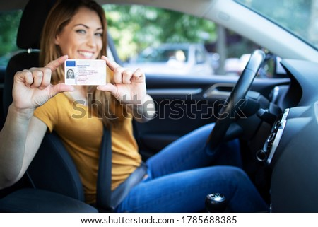 Driving school. Young beautiful woman successfully passed driving school test. Female smiling and holding driver's license. Girl with driving license.