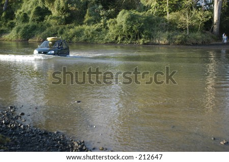 Driving small car through deep river in Costa Rica with surfboards on roof