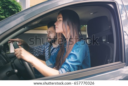 Driving test. Young serious woman driving car feeling inexperienced, looking nervous at the road traffic for information to make appropriate decisions. Man is an instructor, controlling and checking #657770326