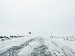 Driving through blizzard snowstorm on black ice and snowy white road and landscape in Norway.