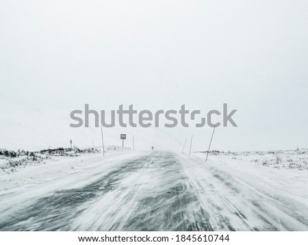 Driving through blizzard snowstorm on black ice and snowy white road and landscape in Norway. Foto stock ©