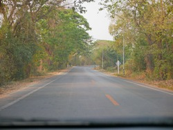 Driving through mixed deciduous forest, typical scenery seen during a long drive in Thailand - driver's perspective, point of view