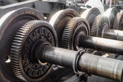 Driving wheelset with gears in a repair depot. Cogwheels of traction gears of traction rolling stock.