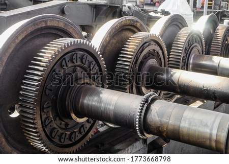 Driving wheelset with gears in a repair depot. Cogwheels of traction gears of traction rolling stock. ストックフォト ©