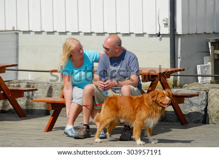 DROBAK, NORWAY - JULY 08, 2006: Unidentified people with a dog rest at the bench in Drobak, Norway.