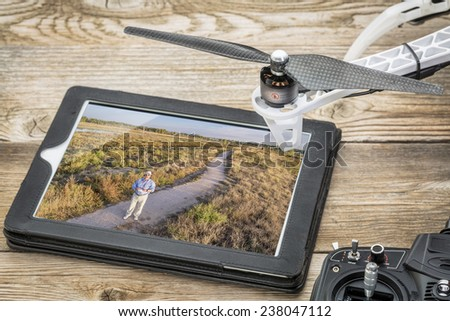 drone aerial photography concept - reviewing aerial picture (drone operator in a field) on a digital tablet with a drone rotor and radio control transmitter,