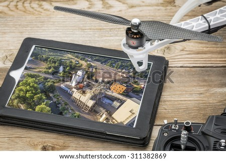 drone aerial photography concept - reviewing aerial picture of grain elevators  on a digital tablet with a drone rotor and radio control transmitter,