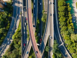 Drone aerial view of curved overpass multi lane highways in daytime summer. Travel tourism and city life transportation concept footage. Trees and green plant around the highway in Shanghai China.