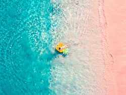 Drone aerial view of girl floating on inflatable pineapple at exotic tropical pink beach