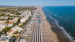 Drone aerial view of the umbrellas and gazebos on Italian sandy beaches. Adriatic coast. Emilia Romagna region