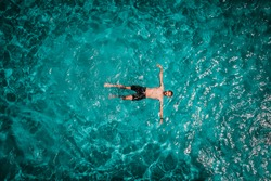 Drone areal view of young male in swimming pool floating