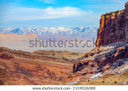 DRONE: Breathtaking flying view snowy mountain range behind a red rocky cliff in the rugged U.S. Wilderness. Flying over the sandstone formations in Utah on a sunny winter day. Spectacular wild nature #1559026088