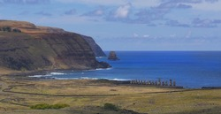 DRONE: Breathtaking view of Ahu Tongariki with tall cliffs and the deep blue ocean in the background. Flying above the vast meadows leading towards a row of mysterious moai sculptures by the shore.