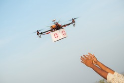 Drone Delivering First Aid Box or medicine to costumer hand during covid-19 or coronavirus lockdown - Advancing Medical Industry Logistics for Drug Transport concept.