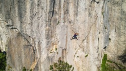 DRONE: Fearless female rock climber learning to top rope looks for a safe hold in the natural wall in Crni Kal. Spectacular drone point of view of an unrecognizable athletic woman learning to climb.
