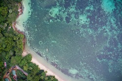 Drone field of view of fishing boats and pristine coastline and forest Praslin, Seychelles.