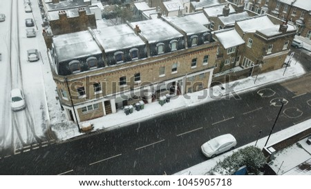 Drone flies forwards over a residential area in South London, England during a rare snow storm in March 2018. Camera is looking out towards a fuzzy horizon.