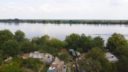 Drone fly over waving river surrounded by local village with various buildings and Wetland and marsh habitat with a reedbed of Common Reed aerial view. Top view.