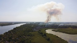 Drone fly over waving river surrounded by local village with various buildings and Wetland and marsh habitat with a reedbed of Common Reed aerial view. Fire in reed marshes