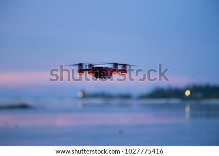 Drone flying at sunset over pink sky in Maldives