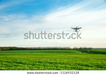 Drone flying over green wheat field in spring. Technology innovation in agricultural industry #1126932128