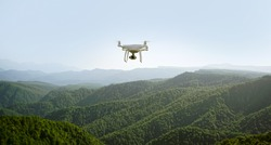 drone flying over mountains. white drone hovering in a bright blue sky. New technology in the aero photo shooting.