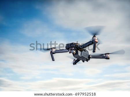 Drone flying overhead in cloudy blue sky #697952518
