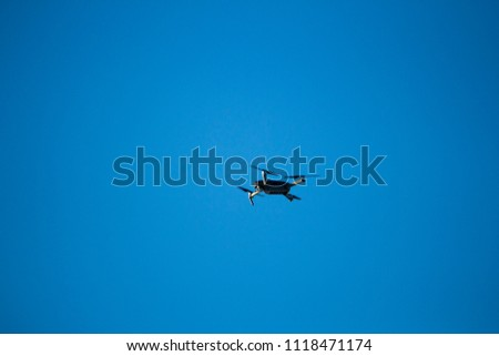 Drone flying to take aerial photo. Silhouette on a clear blue sky.
