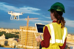 Drone inspection. Operator inspecting construction building site flying with drone