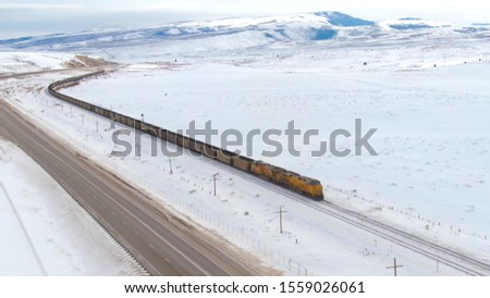 DRONE: Locomotive transports a long line of railcars full of coal across the idyllic wintry United States. Freight train moves along a highway while transporting cargo from coal mine to storage depot. #1559026061