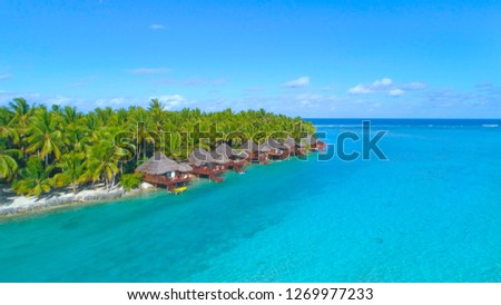 DRONE: Lush palm trees surround the oceanfront bungalows in sunny Cook Islands. Flying away from the remote tropical island in stunning turquoise ocean. Luxury overwater villas in beautiful Aitutaki.