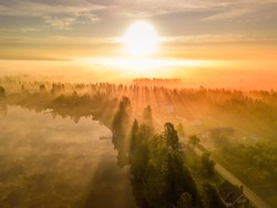 drone photo of foggy sunrise over forest, lake an village in North Sweden - golden sun light with beams and shadows. Västerbotten,  West Bothnia province, north of Sweden