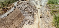 Drone photo on construction of new highway - many heavy industrial machines work together - dump trucks, bulldozer and excavator remove and move exploded stones from mountain base in pine tree forest